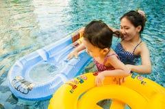 使用与与她的母亲的游泳圆环的年轻俏丽的女孩 免版税库存照片