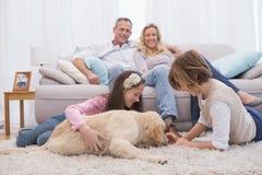 使用与与他们的父母的狗的逗人喜爱的兄弟姐妹沙发的 免版税库存照片