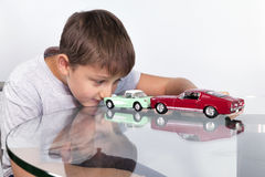 使用与两辆玩具汽车的男孩 库存图片