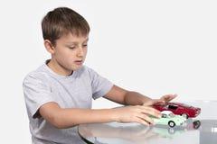 使用与两辆玩具汽车的男孩 免版税库存图片