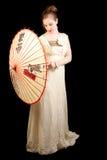 使用与中国伞的维多利亚女王时代的礼服的女孩 免版税图库摄影