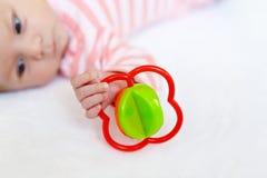 使用与五颜六色的吵闹声玩具的逗人喜爱的女婴 库存照片