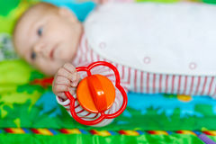 使用与五颜六色的吵闹声玩具的逗人喜爱的女婴 免版税图库摄影