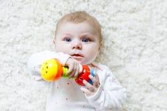 使用与五颜六色的吵闹声玩具的逗人喜爱的女婴 图库摄影