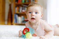 使用与五颜六色的吵闹声的逗人喜爱的女婴戏弄 免版税库存照片