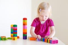 使用与五颜六色的块的逗人喜爱的小孩女孩 免版税库存图片