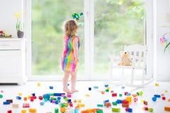 使用与五颜六色的块的逗人喜爱的笑的小孩女孩 免版税库存图片