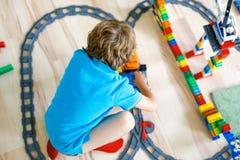 使用与五颜六色的塑料块和创造火车站的小白肤金发的孩子男孩 库存照片
