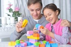 使用与五颜六色的塑料块的兄弟和姐妹 库存照片
