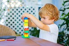使用与五颜六色的塑料块的小孩男孩 库存图片