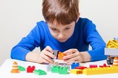 使用与五颜六色的塑料建筑玩具块的孩子在桌上 免版税库存照片