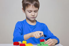 使用与五颜六色的塑料建筑玩具块的小孩男孩在桌上 库存照片