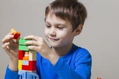 使用与五颜六色的塑料建筑玩具块的愉快的孩子在桌上 库存图片