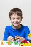 使用与五颜六色的塑料建筑玩具块的愉快的孩子在桌上 免版税库存图片
