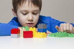 使用与五颜六色的塑料建筑玩具的小孩男孩在家阻拦 免版税库存照片