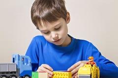 使用与五颜六色的塑料建筑的被集中的孩子戏弄在桌上 关闭 免版税图库摄影