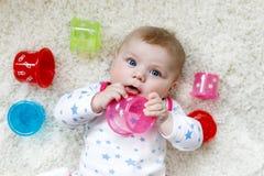使用与五颜六色的教育吵闹声玩具的逗人喜爱的可爱的新出生的婴孩 免版税库存照片