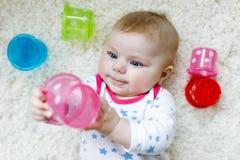 使用与五颜六色的教育吵闹声玩具的逗人喜爱的可爱的新出生的婴孩 图库摄影