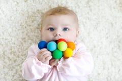 使用与五颜六色的木吵闹声玩具的逗人喜爱的女婴 免版税库存照片
