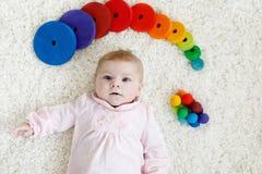使用与五颜六色的木吵闹声玩具的逗人喜爱的女婴 库存照片