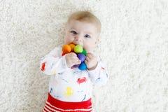 使用与五颜六色的木吵闹声玩具的逗人喜爱的女婴 库存图片