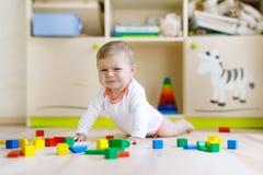 使用与五颜六色的木块的逗人喜爱的哀伤的哭泣的婴孩戏弄 免版税库存照片