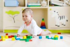 使用与五颜六色的木块的逗人喜爱的哀伤的哭泣的婴孩戏弄 库存照片