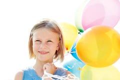 使用与五颜六色的气球的愉快的孩子 免版税库存照片