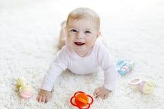 使用与五颜六色的淡色葡萄酒吵闹声玩具的逗人喜爱的女婴 图库摄影