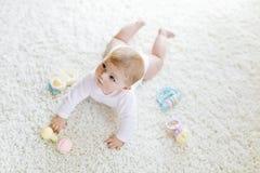 使用与五颜六色的淡色葡萄酒吵闹声玩具的逗人喜爱的女婴 库存图片