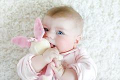 使用与五颜六色的淡色葡萄酒吵闹声玩具的逗人喜爱的女婴 库存照片