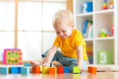 使用与五颜六色的玩具块的学龄前儿童孩子 哄骗使用与教育木玩具在幼儿园或日托中心 T 免版税库存照片
