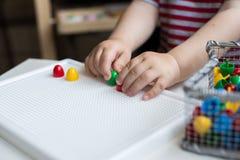 使用与五颜六色的玩具的孩子坐在窗口 男孩一点 免版税库存图片