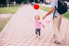 使用与五颜六色的玩具的愉快的小女孩迅速增加户外 免版税库存照片