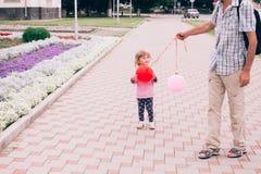 使用与五颜六色的玩具的愉快的小女孩迅速增加户外 图库摄影