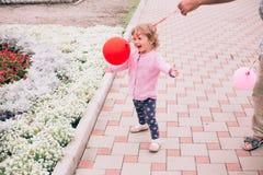 使用与五颜六色的玩具的愉快的小女孩迅速增加户外 免版税库存图片