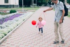 使用与五颜六色的玩具的愉快的小女孩迅速增加户外 免版税图库摄影