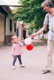 使用与五颜六色的玩具的愉快的小女孩迅速增加户外 库存照片