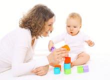 使用与五颜六色的玩具的母亲和婴孩 免版税库存照片