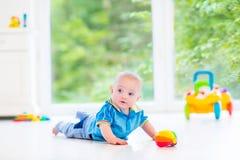 使用与五颜六色的球和玩具汽车的可爱的男婴 库存图片