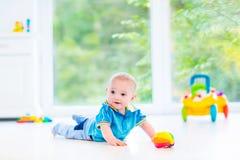 使用与五颜六色的球和玩具汽车的滑稽的男婴 免版税库存图片