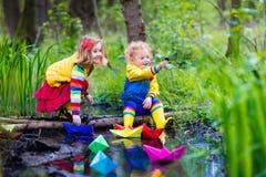 使用与五颜六色的纸小船的孩子在公园 免版税库存图片