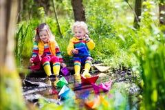 使用与五颜六色的纸小船的孩子在公园 免版税库存照片