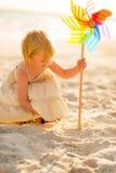 使用与五颜六色的风车玩具的女婴 免版税图库摄影