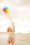 使用与五颜六色的风车玩具的愉快的女婴 免版税库存照片