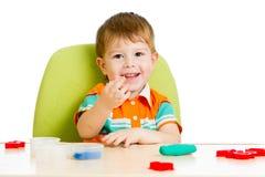 使用与五颜六色的黏土的愉快的儿童男孩 免版税库存照片