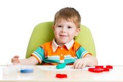 使用与五颜六色的黏土的愉快的小孩 图库摄影