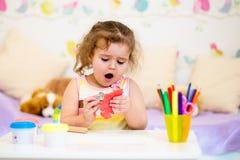 使用与五颜六色的黏土的孩子 免版税库存图片
