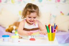 使用与五颜六色的黏土的小孩 免版税库存照片