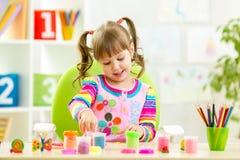 使用与五颜六色的黏土的小孩 免版税库存图片